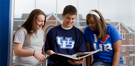 Three students talking and looking at a book.