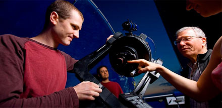 Students and professor working with a telescope.