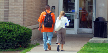 Two students walking into a campus building.