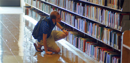 Student searching for a book in the library.